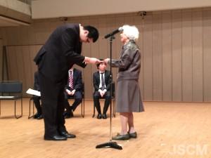 旭井翔一さんに冨樫賞の目録を渡す、故・富樫康夫人の敏子さん。